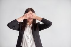 Woman in a suit, blocking her eyes, business compliance concept royalty free stock photo