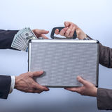 Woman in suit giving briefcase with dollars to man Stock Photos