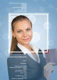 Woman in suit, holding passport, looking at camera, smiling Royalty Free Stock Image
