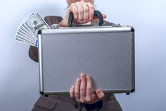 Woman in suit holds metal briefcase with dollars Royalty Free Stock Images