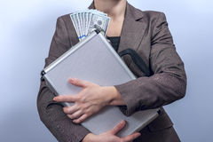 Woman in suit holds metal briefcase with dollars Royalty Free Stock Photography