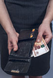 Woman in suit with leather purse full of money Stock Photos