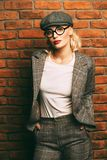 Woman in suit. Portrait of a sexual young woman wearing checkered suit, cap and glasses. Beautiful smart girl. Beauty, fashion royalty free stock image