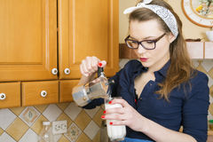 Woman at suit pours coffee in milk Stock Images