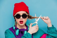 Woman in suit of 90s with headphones and scissors. Portrait of a woman in red hat, sunglasses and suit of 90s with headphones and scissors on blue and pink royalty free stock photography