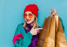 Woman in suit of 90s with shopping bags. Portrait of a woman in red hat, sunglasses and suit of 90s with shopping bags on blue and pink background stock photo