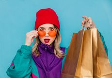 Woman in suit of 90s with shopping bags. Portrait of a woman in red hat, sunglasses and suit of 90s with shopping bags on blue and pink background royalty free stock images