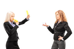 Woman in suit showing a yellow card and blowing a whistle to a f Stock Photo