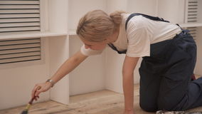 Woman in suit standing on knees, and covers the floor varnish brush. Repairman with white hair and is bent over by the tool causes the emulsion on a wooden stock footage