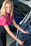 Woman with suitcase. Travelling woman take suitcase from a car Stock Image
