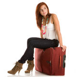 Woman with suitcase. Young woman sitting on her suitcase Royalty Free Stock Images
