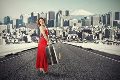 Woman with suitcase baggage standing on road waiting for ride. Portrait beautiful young woman with suitcase baggage standing on road waiting for a ride isolated Stock Image