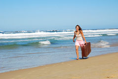 Woman with suitcase on beach stock images