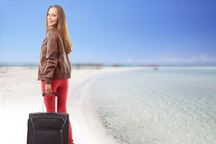 Woman with a suitcase on the beach Stock Images