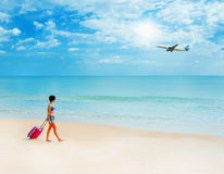Woman with a suitcase on the beach Royalty Free Stock Images