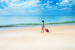 Woman with a suitcase on the beach Stock Photos