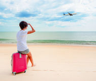 Woman with a suitcase on the beach Stock Photo