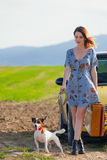 Woman with suitcase and dog near car royalty free stock photography