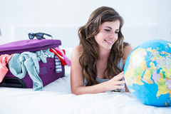Woman with a suitcase and globe while lying on her bed Stock Images