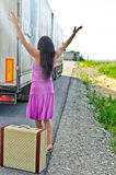 Woman with suitcase hitchhiking. A car Royalty Free Stock Photo