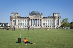 Woman with suitcase laying in front of  Reichstag building in Berlin Royalty Free Stock Photography