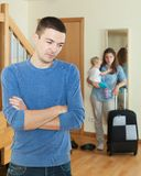 Woman with suitcase leaving home Stock Images