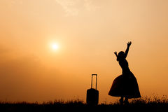 Woman with a suitcase on a meadow  at sunset silhouette. Stock Images