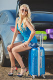 A woman with a suitcase near the car. Woman with the suitcase near the car. beautiful woman relaxes leaning against a luxurycar Stock Photography