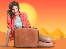 Woman with suitcase over a background drawing of pyramids Royalty Free Stock Photo