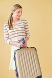 Woman With Suitcase And Passport Looking Away Against Colored Ba Stock Photography