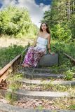 Woman on a suitcase at the railroad Stock Photo