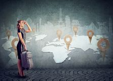 Woman with suitcase ready to explore the world on landmarks map background. Young woman with suitcase ready to explore the world on landmarks map background royalty free stock photos