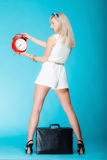 Woman with suitcase red clock. Travel time management concept. Stock Image