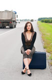 Woman with suitcase on road Royalty Free Stock Image