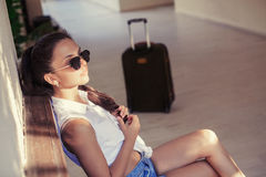 Woman with a suitcase sits and waits Stock Image
