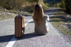 The woman with the suitcase sitting on the asphalt waits to resume the journey by hitchhiking. Traveling, by any means, it is important to travel Stock Photos