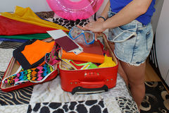 Woman with suitcase sitting on bed in hotel. Young Girl packing bag for travel, closing hardly overflowing luggage suitcase Royalty Free Stock Images