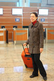 Woman with suitcase standing at airport Stock Photography