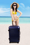 Woman with suitcase standing at beach Stock Image