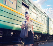 Woman with a suitcase standing on the platform Royalty Free Stock Photo