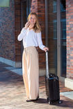 Woman with suitcase talking by the phone Royalty Free Stock Images