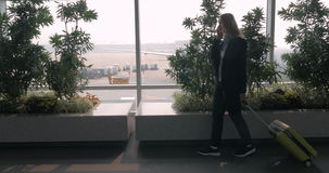 Woman with suitcase talking on phone and walking in airport terminal stock footage