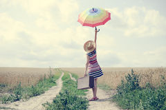 Woman with suitcase and umbrella standing on road. Woman with suitcase standing on road between field of wheat. Backview of girl in hat rising umbrella Royalty Free Stock Photography