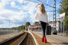 Woman with suitcase waiting in station Stock Photography