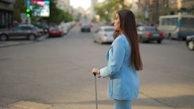 Woman with suitcase waiting taxi in a city. Woman with suitcase waiting taxi in the city near road stock video footage