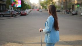 Woman with suitcase waiting taxi in a city. Woman with suitcase waiting taxi in the city near road stock footage
