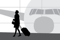 Woman with suitcase walking in airport Royalty Free Stock Images