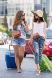 Woman with a suitcase walking down the road. Two young women with suitcases. Vacation concept. Car trip. Summer vacation. Best friend posing with their luggage Stock Image