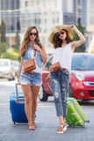 Woman with a suitcase walking down the road. Two young women with suitcases. Vacation concept. Car trip. Summer vacation. Best friend posing with their luggage Stock Photo