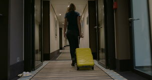 Woman with suitcase walking in hotel corridor stock video footage
